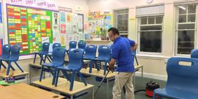 Mann reinigt Klassenzimmer