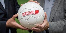 """Vier Hände halten einen weißen Lederfußball mit der Aufschrift """"Gesetzliche Rente stärken: Der Ball liegt in Ihrem Feld""""; daneben das DGB-Logo"""