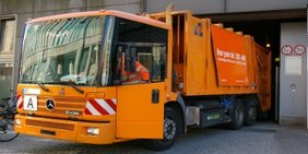 Ein Oranges Müllauto fährt auf die Strasse.