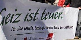 Transparent mit der Aufschrift: Geiz ist teuer. Für eine soziale, ökologische und faire Beschaffung